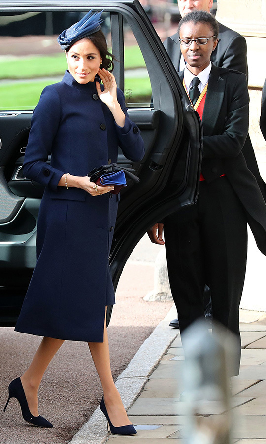 The duchess was back in her go-to Givenchy for Princess Eugenie and Jack Brooksbank's royal wedding, pairing a navy coat dress with a hat by London-based milliner Noel Stewart, a blue and burgundy clutch and suede pumps. She wore her hair pulled back in a loose chignon and, unknown to fans at the time, was rocking that inimitable pregnancy glow!