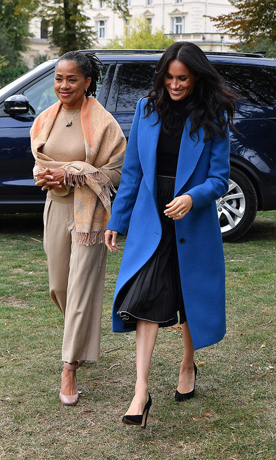 Meghan couldn't stop beaming as she arrived at the launch of her first solo charity project, <em>Together: Our Community Cookbook</em>, with mom Doria Ragland on Sept. 20. The Duchess of Sussex was the picture of chic in a blue peaked lapel coat by Canada's own SMYTHE, a pleated skirt by her pal Misha Nonoo and a TUXE Bodywear turtleneck bodysuit. Anchoring the look was a pair of Sarah Flint heals and she topped it off with beautiful, bouncy soft waves a la Duchess Kate!