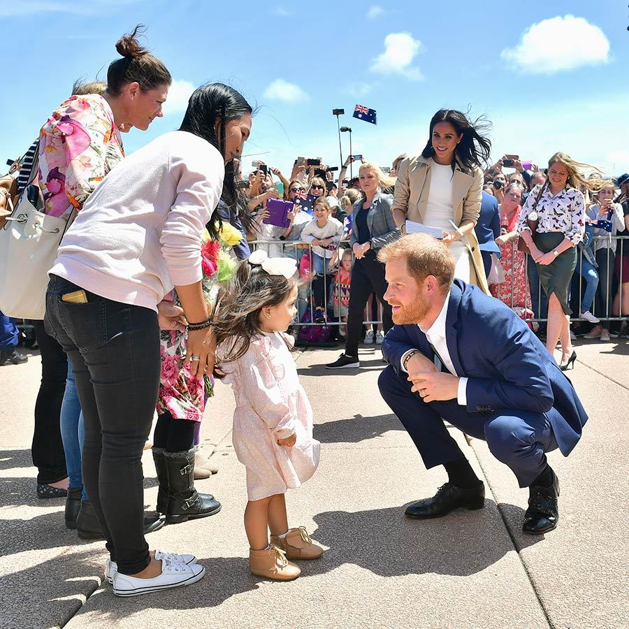 Their royal walkabout at the Sydney Opera House was definitely one for the books! Meghan, dressed in a pretty white dress and trend coat, joined her husband in greeting the cutest little girls, who gave them bouquets of flowers.