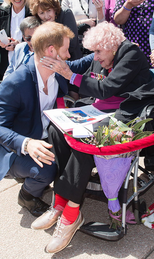"Prince Harry met with 98-year-old Daphne Dunne in 2015 and 2017 while in Sydney. Now, it's become tradition to say ""hello"" to the woman during this exact walkabout! He knelt down beside his elderly friend to chat, after which he called over his newly pregnant wife to meet her, too.