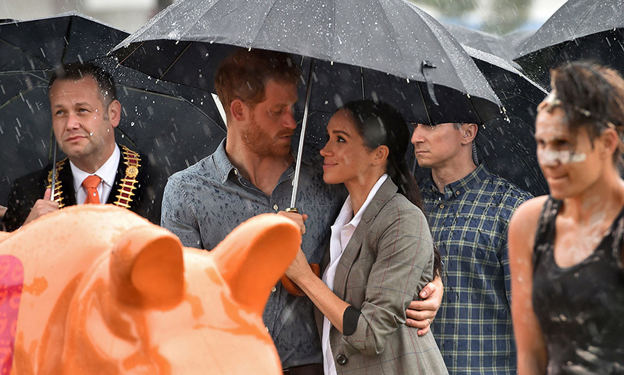 Harry and Meghan only had eyes for each other as they cozied up beneath an umbrella at a community bbq in Dubbo, Australia on Oct. 17.