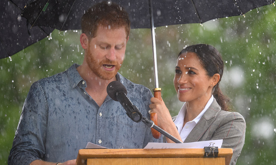 Mom-to-be Meghan couldn't help but smile as she watched her husband give an impassioned speech in Dubbo. She sweetly held an umbrella over his head the entire time.