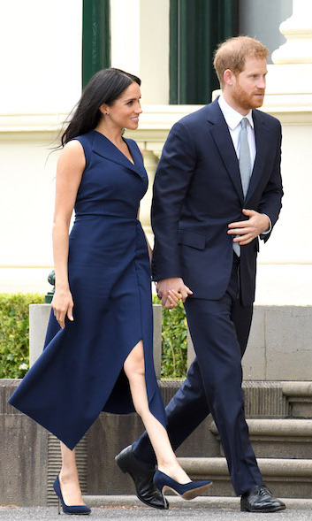 Meghan removed her trench to reveal the stunning details of her Dion Lee dress, which boasts an asymmetrical neckline and a side slit.