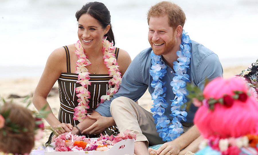 "The Sussexes' vibe was all love as they sat barefoot in the sands of Bondi Beach on Friday (Oct. 19). Meghan tenderly held on to Harry's arm while they participated in an ""anti bad vibe circle"" with OneWave, a surfing group that uses fun techniques to break the stigma of metal health issues. It was ""Fluro Friday,"" so the members were dressed to impress in bright colours, wigs, metallics and more!