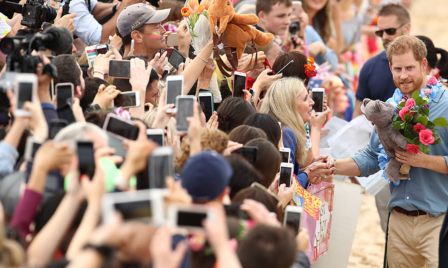 During a walkabout on Bondi Beach, Prince Harry was gifted a grey bear stuffed animal while another fan passed a plush kangaroo-shaped backpack through the crowd. 