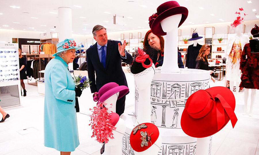 The Queen was radiant in a Tiffany blue ensemble as she perused the hat selection at Fenwick department store in the Lexicon shopping centre on Oct. 19. 