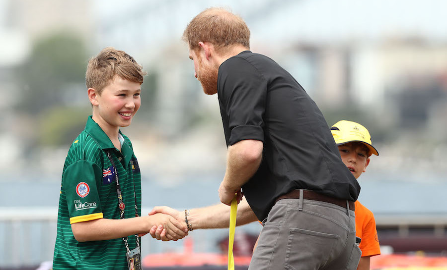 Showing off his charm, the duke happily shook the hand of one of the winners before handing him his medal.