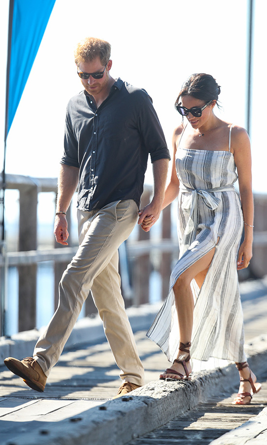 Meghan opted for a casual cool look that paired a striped Reformation Pineapple dress, complete with a daring slit, with Sarah Flint's Grear sandals. The pregnant royal finished the look with large black sunnies, a bronzed complexion and her signature messy bun. She and Prince Harry sweetly held hands as they walked.