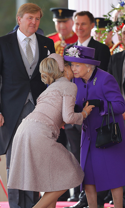 The two queens shared a cheek kiss, too, as King Willem-Alexander looked on. Her Majesty looked lovely as ever in bright, royal purple!