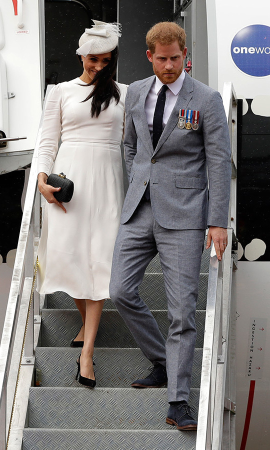 The Sussexes touched down in Fiji on Oct. 23 as they kicked off the second week of their royal tour. The couple will spend three days on the gorgeous island, making the historic Grand Pacific Hotel their home base. On arrival at Suva's Nausori airport on a Qantas flight, the couple was greeted by some rain and winds - but also the Hon Frank Bainamara, Fiji's Prime Minister and his wife, Maria, leader of the opposition Ro Teimumu Kepa, Alessandro Truppia, the High Commissioner's wife and Rear Admiral Viliame Naupoto, commander of the RFMF. They also met High Commissioner Melanie Hopkins and chief of protocol Jonetani Tagivetaua. The red carpets may have been blowing in the wind, but that didn't stop the Fijian people from giving the couple an unforgettable traditional welcome!