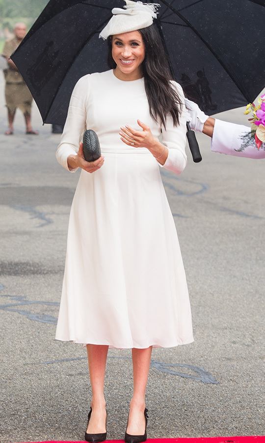 Though she wore casual clothes on the flight, Meghan dressed up for her arrival, pairing a white long-sleeved Zimmermann dress with black Tabitha Simmons pumps, a Kayu clutch and a Stephen Jones hat (which threatened to fly away in the wind!). She had her hair blown out and a beautiful bronzed glow on her skin as she stood under an umbrella.
