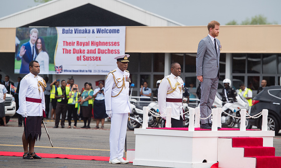During the royal salute and national anthem, Prince Harry stood at attention on the dais.