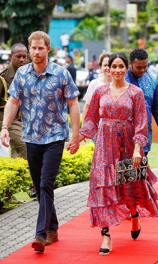 Meghan wore a beautiful ruffled Figue dress on the second day of the couple's tour in Fiji, the red-and-blue floral Frederica wrap style number with pom poms on the belt, which retails for $1950. She anchored the look with her Castaner espadrilles and carried an oversized clutch. The duchess wore flowers in her hair, which she styled in a messy bun with tendrils tucked behind her ears. She was perfectly complemented by Prince Harry in his Bula shirt!