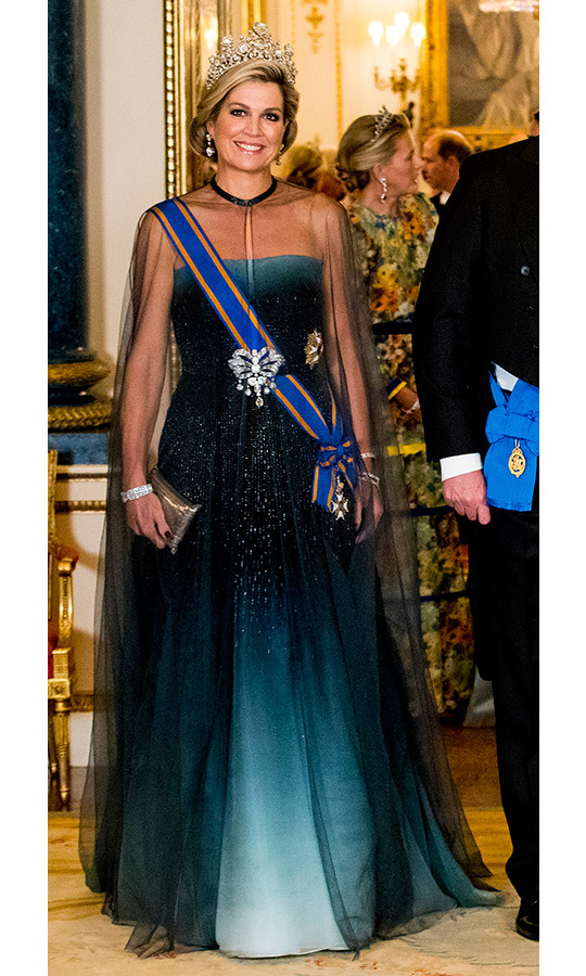 Queen Maxima wore a stunning black and teal ombre gown with a sheer cape and carried a small metallic clutch. She wore her hair in a chic updo and wore a number of  brooches and a sash. 
