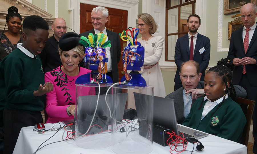 The Dutch queen and Prince Edward interacted with school children as they worked on the Ohbot, an educational robotics system.