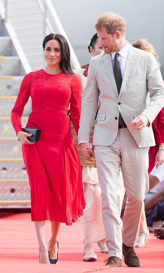 Fresh off the plane from Fiji, where they enjoyed a night on an exclusive island before unveiling a statue at at Nadi airport, Prince Harry and Meghan arrived in Tonga on Oct. 25 ready to explore the third country on their 16-day tour. The duchess looked stunning in a pleated and embroidered Self-Portrait dress (in the perfect shade of Tongan red!) plus her beloved navy Manolo Blahnik BB pumps and Dior clutch. She wore a few rings by Canadian eco-brand Ecksand on her fingers and her sleek locks cascading over her shoulders. Prince Harry looked island-ready in a beige linen suit and olive-green tie.