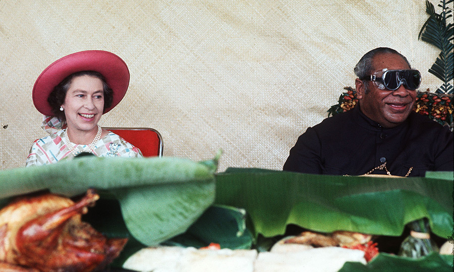 The Queen was all smiles as she sat down for a feast with King Tāufaʻāhau Tupou IV in 1977. The royal succeeded to the throne when his mother, Queen Salote, passed away in 1965.