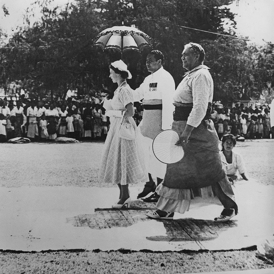 The two queens walked on a carpet of tapa cloth as they left the Mala'e, or feast house, on Her Majesty's first visit to Tonga. The London native was shaded from the sun's rays by an umbrella.