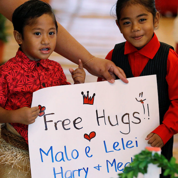 Free hugs for Meghan and Harry! Two adorable kids welcomed the royal couple with the sweetest sign ever.