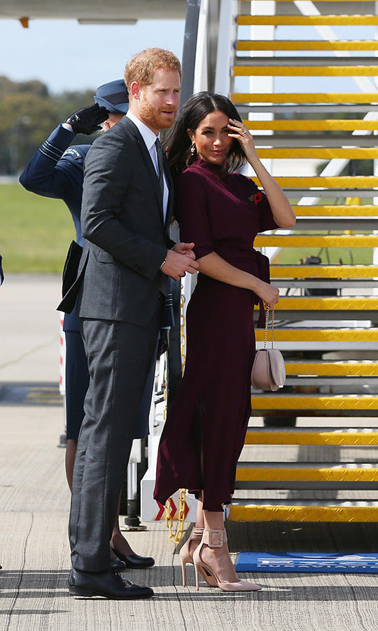 As she bid Australia adieu, Meghan wore an oxblood BOSS by Hugo Boss midi jersey dress with a high neckline and half sleeves. She paired it with peach-hued Aquazzura Casablanca pumps and a matching Cuyana bag.  The duchess's hair, styled in soft waves, was blowing in the wind as she boarded the plane for the final leg of the couple's 16-day tour! Prince Harry wore a dark suit and matching tie. 