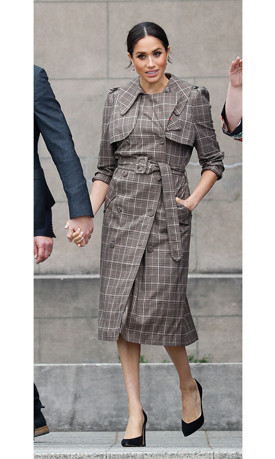 Wearing a checked trench by New Zealand designer Karen Walker, Meghan was ready to explore the final country on the Sussexes' royal tour. She wore the coat over a simple black ASOS dress and anchored the look with her Sarah Flint Jay pumps. Yellow drop earrings dangled from her ears, beautifully showcased courtesy of her sleek bun, and the bronzed beauty had her eyes accentuated by dark liner and mascara. 
