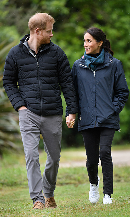 "Earlier that day, the parents-to-be enjoyed a romantic and quiet walk through Abel Tasman Park. Meghan looked perfectly dressed for the overcast weather with Outland Denim's black ""Harriet"" jeans, which she was wearing earlier, a blue weatherproof jacket by Seasalt Cornwall, the same black turtleneck and faux leather sneakers by Stella McCartney x Adidas.