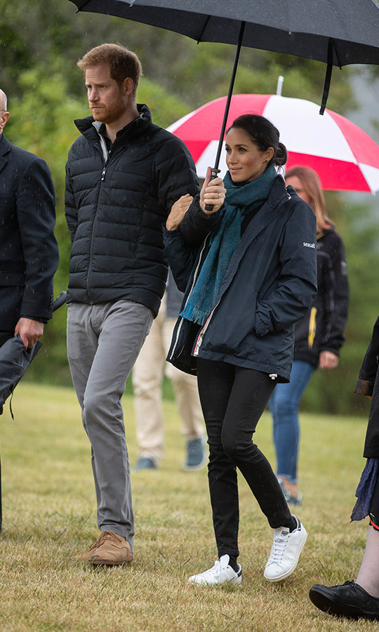 The day's rainy weather forced the couple to cut their visit short, but they were still able to meet with locals and explore the park and its beach. Meghan traded her Club Monaco coat for a windbreaker by Seasalt Cornwall, which she wore with a green scarf, her Outland Denim Harriet jeans and white faux leather sneakers by Stella McCartney for Adidas. Prince Harry wore his grey pants and beige shoes with a black puffer jacket as the two cozied up under an umbrella.