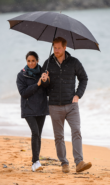 Prince Harry took his turn holding the umbrella up for his wife!