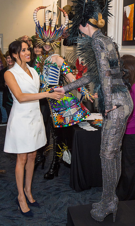Meghan met with actors aspiring to work in the film industry in New Zealand, including this towering figure in a glitzy silver jumpsuit festooned with feathers. 