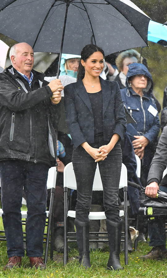 Meghan watched the dedication as someone graciously held an umbrella over her head to keep the rain at bay. The royal wore a navy cropped blazer by NZ designer Karen Walker with a black t-shirt, skinny J. Crew jeans and Muck's 'Reign' boots.