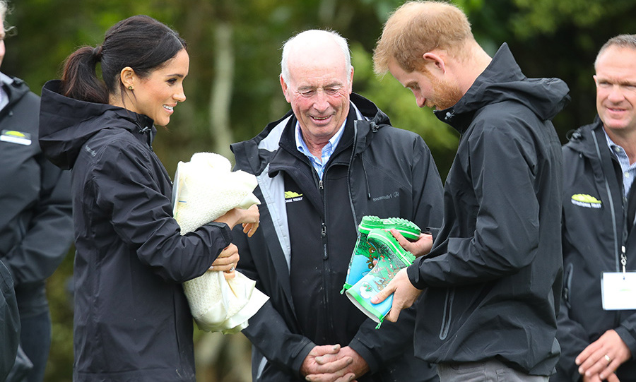The parents-to-be received the most adorable pair of kids' rainboots animated with a nature cartoon scene - a fitting gift as the couple braved the rain in waterproof Muck Boots. Meghan is also holding a blanket and baby book.