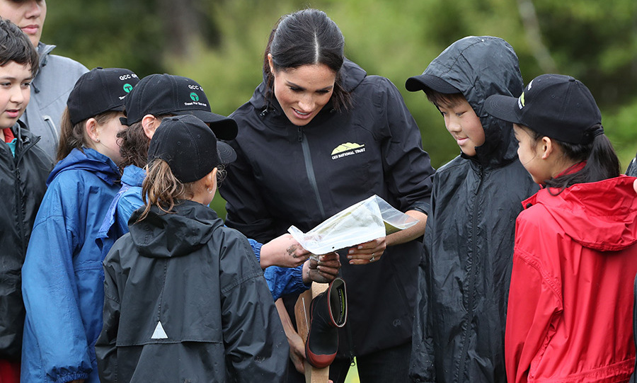 Meghan looked over one of her gifts, a special book, with the children from Trees For Survival.