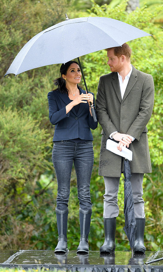 Prince Harry couldn't take his eyes off his beautiful wife. The duke looked sharp in grey pants, an olive coat and white shirt, topped off with Muck Boots.
