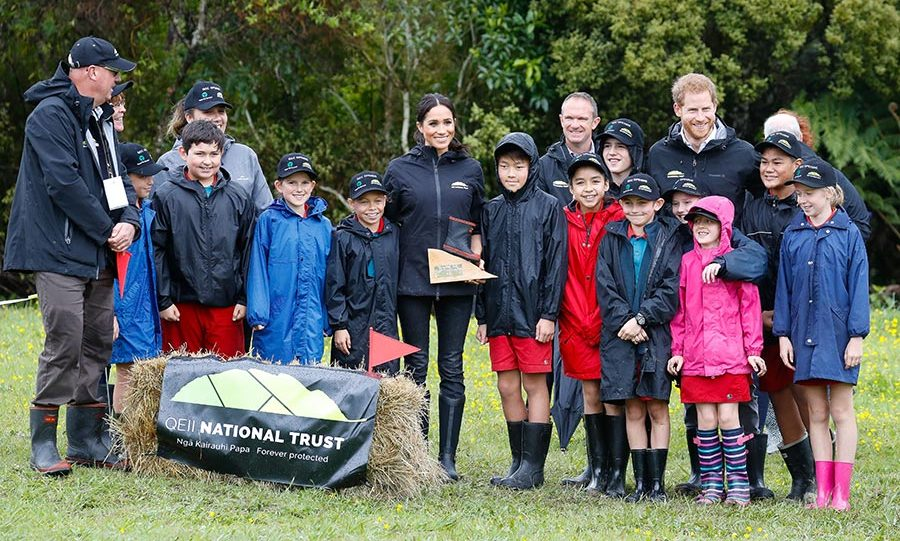 The Sussexes posed for a group photo with the group from Trees For Survival - part of the future generation of conservationists. Meghan proudly held up the trophy from their welly-wanging competition, which she won!