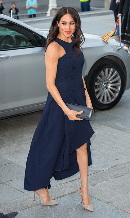 For a reception hosted by Prime Minister Jacinda Ardern at the Auckland War Memorial Museum, Duchess Meghan dusted off an old favourite – the dress she wore to her first event with Prince Harry! She dazzled in a navy-blue Antonio Berardi ruffle midi dress, paired with Aquazzura 'Deneuve' nude suede pumps. She accessorized with a pair of small earrings and a navy clutch, keeping her hair curled by her shoulders and popping on a swipe of bright pink gloss.