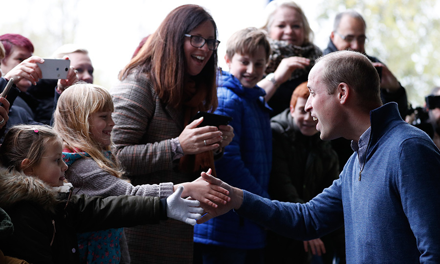 Prince William shook hands with two little girls during a walkabout outside the building.