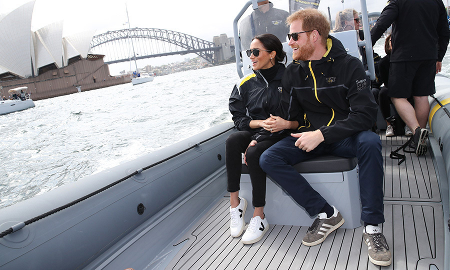 Meghan traded her white pinstripe blazer for an official Invictus Games windbreaker, perfect for hitting the waters around Sydney Harbour to take in a sailing competition. She popped on a pair of crisp white Veja sneakers and the Gravier sunnies by New Orleans brand KREWE eyewear. Prince Harry wore his Invictus jacket and blue pants with Adidas sneakers.