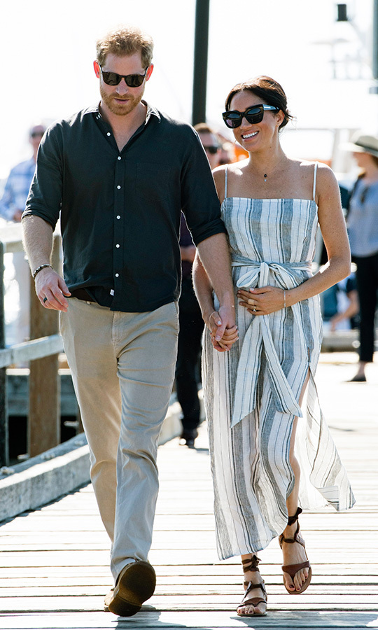 To meet fans in Kingfisher Bay Jetty on Fraser Island, Meghan opted for a casual cool look that paired a striped Reformation Pineapple dress, complete with a daring slit, with Sarah Flint's Grear sandals. The pregnant royal finished the look with large black sunnies, a bronzed complexion and her signature messy bun. 