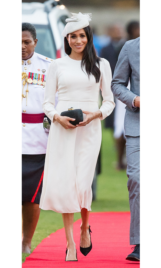 Australian label Zimmermann was behind the prim white dress that Meghan wore on arrival in Fiji on Oct. 23, alongside her Tabitha Simmons slingbacks, a Kayu clutch and a pretty Stephen Jones headpiece featuring ribbons and net. Her jewellery was borrowed from the Queen and Prince Charles. The mom-to-be wore her layered locks blown straight and her skin luminous with a pink lip and lined eyes. 
