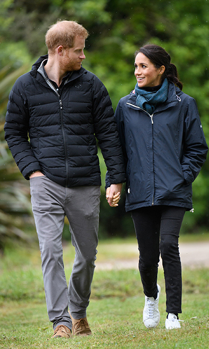 "The parents-to-be enjoyed a romantic and quiet walk through Abel Tasman Park. Meghan looked perfectly dressed for the overcast weather with Outland Denim's black ""Harriet"" jeans, which she was wearing earlier, a blue weatherproof jacket by Seasalt Cornwall, the same black turtleneck and faux leather sneakers by Stella McCartney x Adidas.