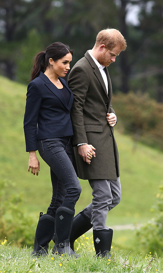 "Prince Harry and Meghan were ready to do some welly-wanging (that's rainboot tossing!) on the North Shore in Auckland as they dedicated a piece of land to the Queen's Commonwealth Canopy. The duchess wore the cropped navy Karen Walker ""Fathom"" blazer with J. Crew skinny jeans and Muck Boots, appropriately called the ""Reign"" style. She wore her hair in her new favourite style, a pretty ponytail with face-framing tendrils, and kept her makeup pretty and natural with rosy cheeks and mascara.