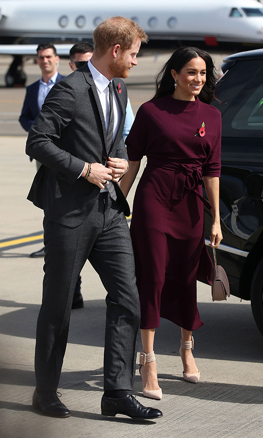 As she bid Australia adieu on Oct. 28 en route to New Zealand, Meghan wore an oxblood BOSS by Hugo Boss midi jersey dress with a high neckline and half sleeves. She paired it with peach-hued Aquazzura Casablanca pumps and a matching Cuyana bag.  The duchess's hair, styled in soft waves, was blowing in the wind as she boarded the plane for the final leg of the couple's 16-day tour!