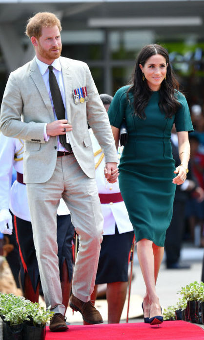 Duchess Meghan looked no further than one of her go-to Canadian designers, Jason Wu, for her day three in Fiji look! The 37-year-old stunned in a hunter green shift dress, along with her trusty navy-blue Manolo Blahnik BB pumps and a bespoke satin Dior clutch. The pregnant royal kept her hair perfectly blown-out by her shoulders, tucked behind her ears to show off a pair of statement gold earrings by Aurelie Bidermann.
