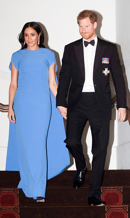 The duchess dazzled at a state dinner on the evening of the couple's arrival in Fiji, turning to German-born, London-based designer Daniela Karnuts for this gorgeous Fijian blue caped gown by her label Safiyaa. She frosted herself with a spectacular pair of borrowed chandelier earrings and a tennis bracelet and anchored the look with a pair of navy pumps. Meghan's hair was parted in the centre with her sleek and shiny locks cascading over her shoulders and she amped up her usual makeup look with rosier cheeks, a smokier eye and lots of luminizer (or is that pregnancy glow?)