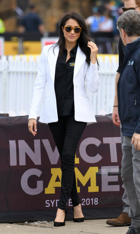For her first official Invictus Games appearance – the Jaguar Land Rover Driving Challenge on Cockatoo Island – Meghan channeled casual-chic in a perfectly tailored white Altuzarra blazer, Mother Denim black skinny jeans and her Invictus polo. She elevated her look by wearing a pair of Tabitha Simmons slingbacks and tortoise shell sunglasses by Illesteva. 