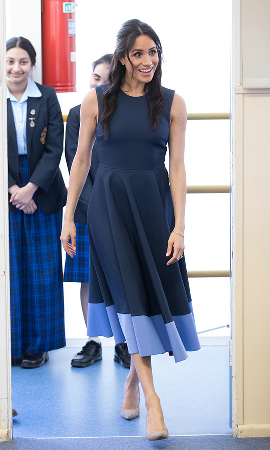 For a surprise visit to an all-girls high school in western Sydney, Meghan swapped her beach dress and espadrilles for another stunning navy dress, this time the sleeveless, colour-block 'Athena' by Serbian designer Roksanda. She anchored the look with nude Stuart Weitzman pumps and tried a new 'do on for size - a half up, half down hairstyle with tendrils framing her face. The former Toronto resident also turned to her Canadian fave Birks for jewellery (the Bee Chic blue topaz earrings and Rosée du Matin White Gold 'Flex Wrap Bracelet'). 