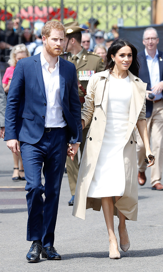 The duchess kept the wind at bay as the Sussexes took a boat ride from Taronga Zoo to the Sydney Opera House by topping her white dress off with a chic trench coat by Aussie Martin Grant. While boarding the boat, the mom-to-be also changed into black flats!