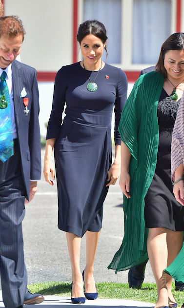 "Duchess Meghan stayed true to her classic sense of style while stepping out for her and Prince Harry's final day on their royal tour. She stunned in a bespoke navy-blue long-sleeved mini Stella McCartney dress, paired with her blue suede Manolo Blahnik ""BB"" pumps, Boh Runga Discologo earrings and a Kiri Nathan Pounamu Necklace.