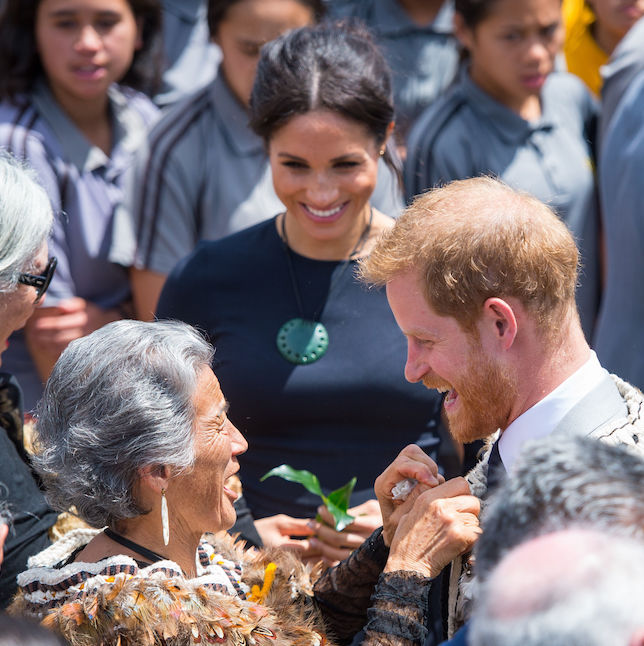 The Duke of Sussex had his traditional Maori cloak (called a Korowai) off by a local as the Duchess of Sussex looked on during their final tour day.