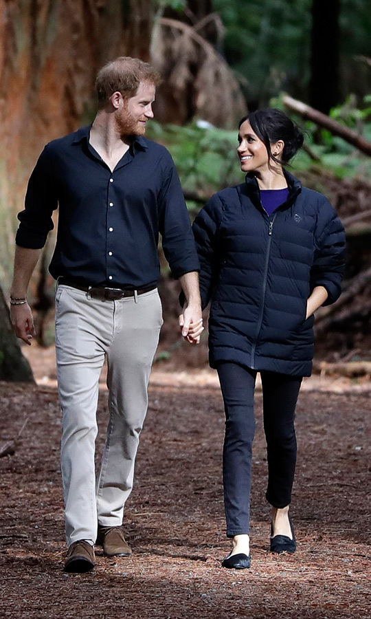 How sweet! Meghan slipped into her husband's Norrøna Oslo Jacket for the last of their 76 royal tour engagements at the Redwoods Treewalk in Rotura, pairing the puffer jacket with her blue Givenchy top from earlier in the day, black jeans and Birdies 'The Starling' slippers. Prince Harry previously wore the warm coat on the beach in Abel Tasman National Park. The duchess donned kept her messy bun with face-framing tendrils in place and her skin was positively radiant as the couple ended the 16-day tour with a final romantic moment. 